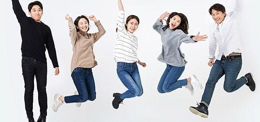 一斉にジャンプしてポーズをきめる友達グループ